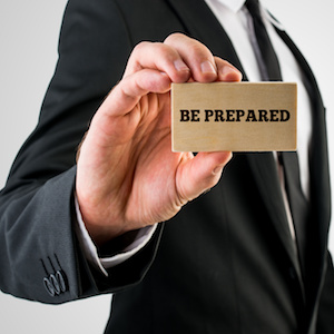 Businessman holding a card saying - Be Prepared
